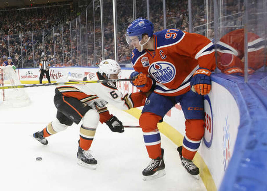 Anaheim Ducks' Simon Despres (6) and Edmonton Oilers' Connor McDavid (97) battle in the corner during the second period of an NHL hockey game Saturday, Dec. 3, 2016, in Edmonton, Alberta. (Jason Franson/The Canadian Press via AP)