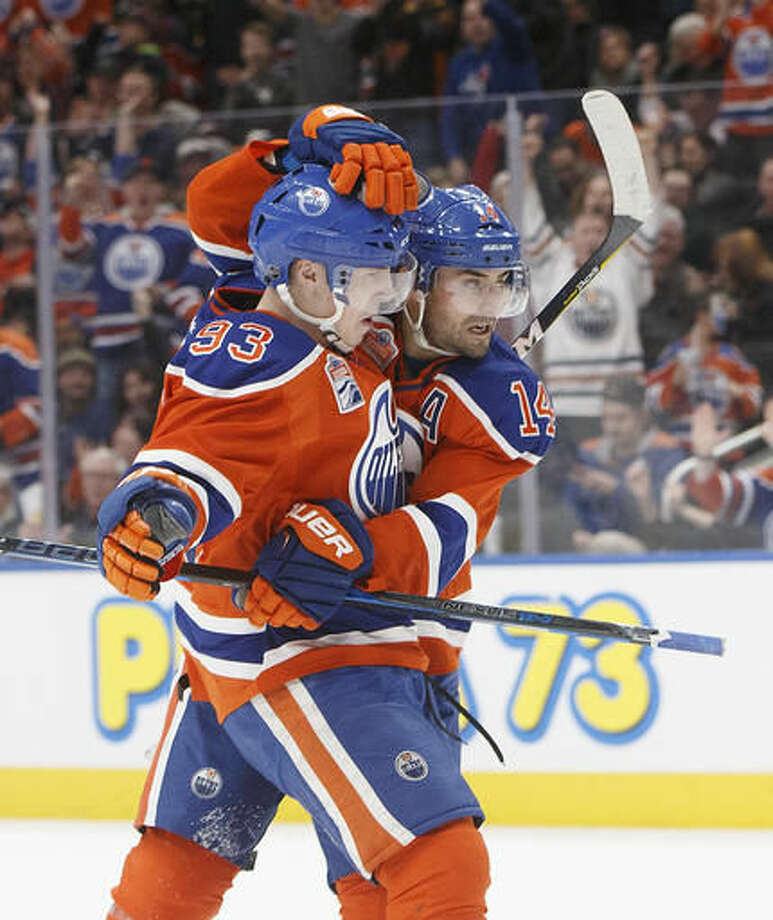 Edmonton Oilers' Ryan Nugent-Hopkins (93) and Jordan Eberle (14) celebrate a goal against the Anaheim Ducks during the second period of an NHL hockey game Saturday, Dec. 3, 2016, in Edmonton, Alberta. (Jason Franson/The Canadian Press via AP)