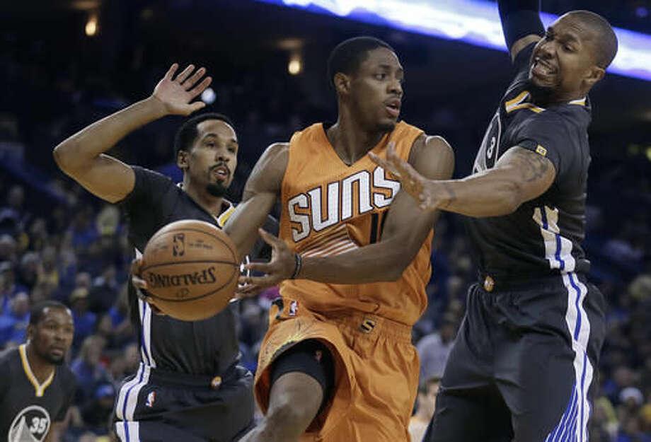Phoenix Suns' Brandon Knight, center, passes between Golden State Warriors' Shaun Livingston, left, and David West (3) during the first half of an NBA basketball game Saturday, Dec. 3, 2016, in Oakland, Calif. (AP Photo/Ben Margot)