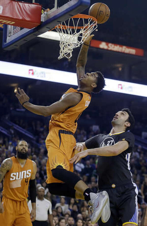 Phoenix Suns' Marquese Chriss lays up a shot over Golden State Warriors' Zaza Pachulia (27) during the first half of an NBA basketball game Saturday, Dec. 3, 2016, in Oakland, Calif. (AP Photo/Ben Margot)