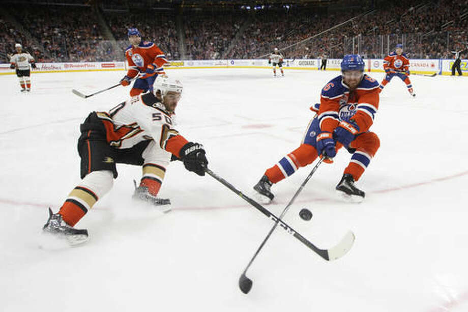 Anaheim Ducks' Antoine Vermette (50) and Edmonton Oilers' Adam Larsson (6) vie for the puck during the first period of an NHL hockey game Saturday, Dec. 3, 2016, in Edmonton, Alberta. (Jason Franson/The Canadian Press via AP)