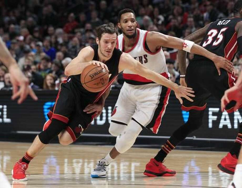 Miami Heat guard Goran Dragic,left, drives on Portland Trail Blazers guard Evan Turner during the first half of an NBA basketball game in Portland, Ore., Saturday, Dec. 3, 2016. (AP Photo/Steve Dipaola)