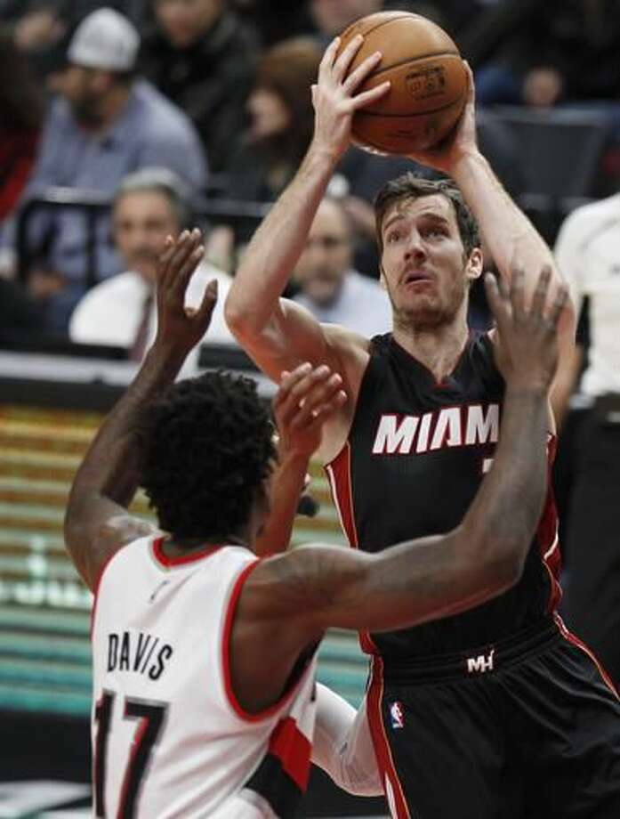 Miami Heat guard Goran Dragic, right, shoots over Portland Trail Blazers forward Ed Davis during the first half of an NBA basketball game in Portland, Ore., Saturday, Dec. 3, 2016. (AP Photo/Steve Dipaola)