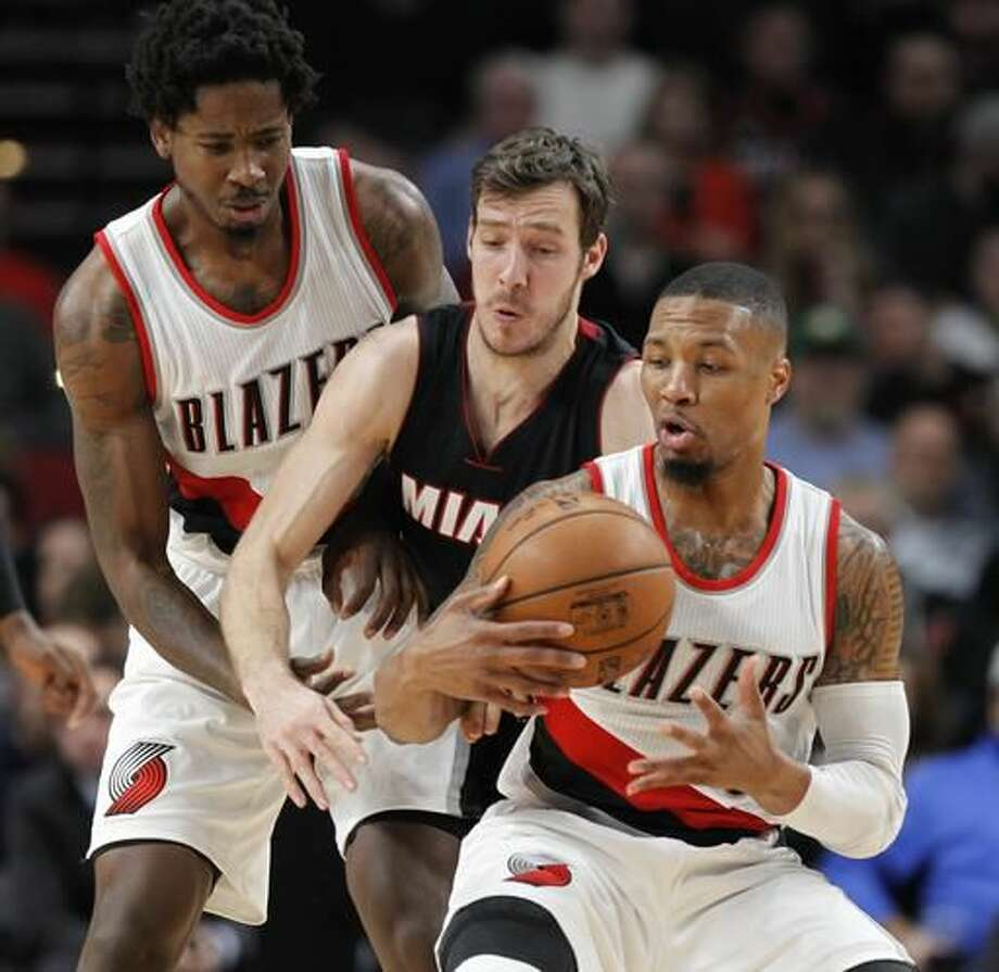 Portland Trail Blazers guard Damian Lillard, right, Miami Heat guard Goran Dragic, center, and Trail Blazers forward Ed Davis reach for the ball during the first half of an NBA basketball game in Portland, Ore., Saturday, Dec. 3, 2016. (AP Photo/Steve Dipaola)