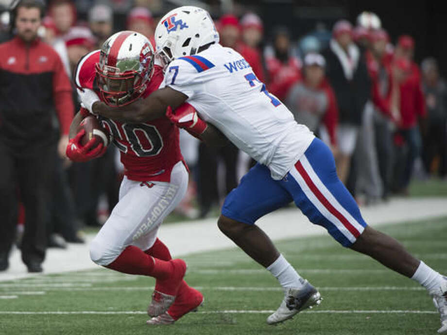 Western Kentucky running back Anthony Wales (20) is tackled by Louisiana Tech safety Xavier Woods (7) in the first half of the Conference USA championship NCAA college football game, Saturday, Dec. 3, 2016, at L.T. Smith Stadium in Bowling Green, Ky. (AP Photo/Michael Noble Jr.)
