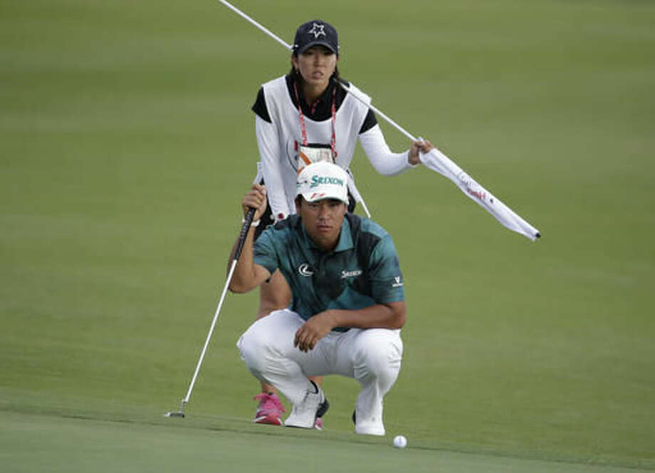 Hideki Matsuyama, of Japan, line sup a putt with his caddie Mei Inul on the 15th hole during the third round at the Hero World Challenge golf tournament, Saturday, Dec. 3, 2016, in Nassau, Bahamas. (AP Photo/Lynne Sladky)
