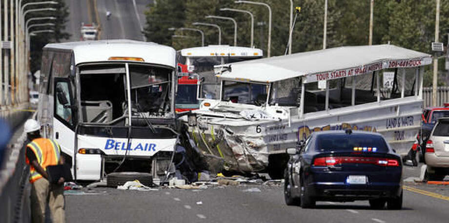 "FILE - In this Sept. 24, 2015, file photo, a ""Ride the Ducks"" amphibious tour bus, right, and a charter bus remain at the scene of a fatal collision on the Aurora Bridge in Seattle. The National Transportation Safety Board meets Tuesday, Nov. 15, 2016, to determine the probable cause of the crash of the Ride the Ducks vehicle after it crossed the center line into oncoming traffic while driving over the bridge. It hit a charter bus full of college students, killing five. (AP Photo/Elaine Thompson, File) Photo: Elaine Thompson"