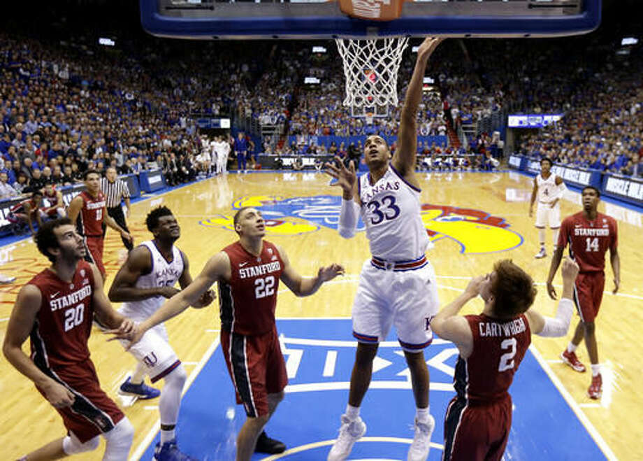 Kansas' Landen Lucas (33) puts up a shot between Stanford's Reid Travis (22) and Robert Cartwright (2) during the first half of an NCAA college basketball game Saturday, Dec. 3, 2016, in Lawrence, Kan. (AP Photo/Charlie Riedel)