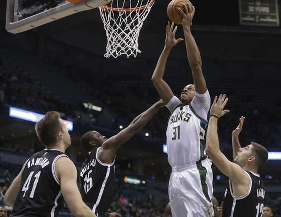 Milwaukee Bucks' John Henson shoots in traffic during the first half of an NBA basketball game against the Brooklyn Nets Saturday, Dec. 3, 2016, in Milwaukee. (AP Photo/Morry Gash)