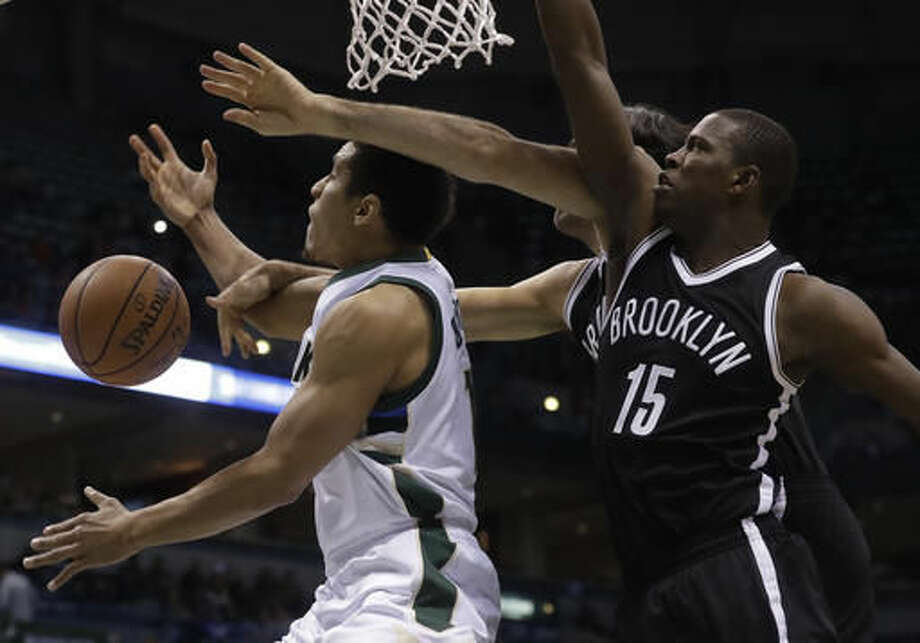 Milwaukee Bucks' Malcolm Brogdon is fouled shooting past Brooklyn Nets' Luis Scola and Isaiah Whitehead (15) during the first half of an NBA basketball game Saturday, Dec. 3, 2016, in Milwaukee. (AP Photo/Morry Gash)