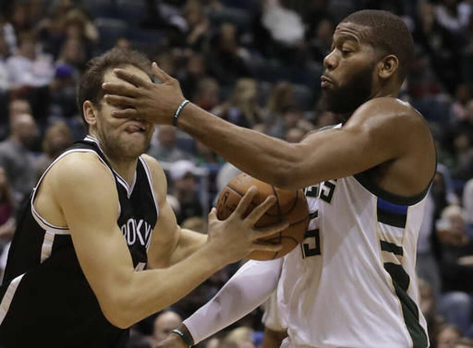Milwaukee Bucks' Greg Monroe fouls Brooklyn Nets' Bojan Bogdanovic during the second half of an NBA basketball game Saturday, Dec. 3, 2016, in Milwaukee. (AP Photo/Morry Gash)