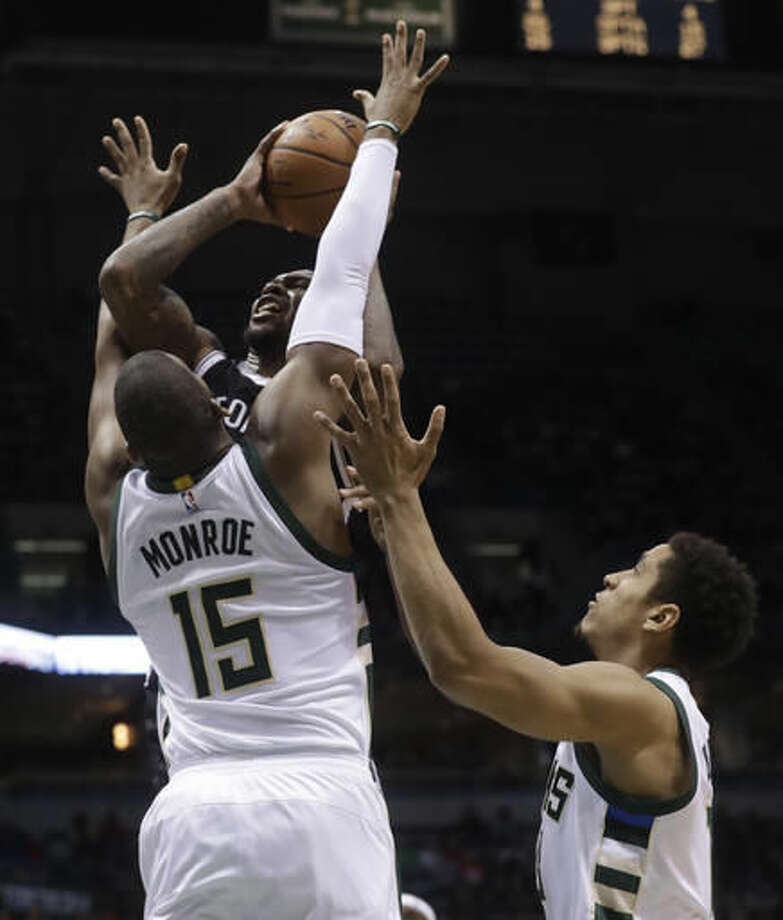 Brooklyn Nets' Sean Kilpatrick is fouled shooting in front of Milwaukee Bucks' Greg Monroe and Malcolm Brogdon during the second half of an NBA basketball game Saturday, Dec. 3, 2016, in Milwaukee. (AP Photo/Morry Gash)