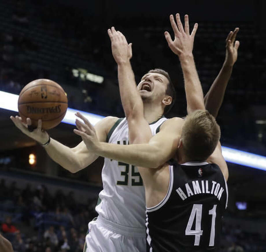 Milwaukee Bucks' Mirza Teletovic is fouled as he shoots past Brooklyn Nets' Justin Hamilton during the first half of an NBA basketball game Saturday, Dec. 3, 2016, in Milwaukee. (AP Photo/Morry Gash)