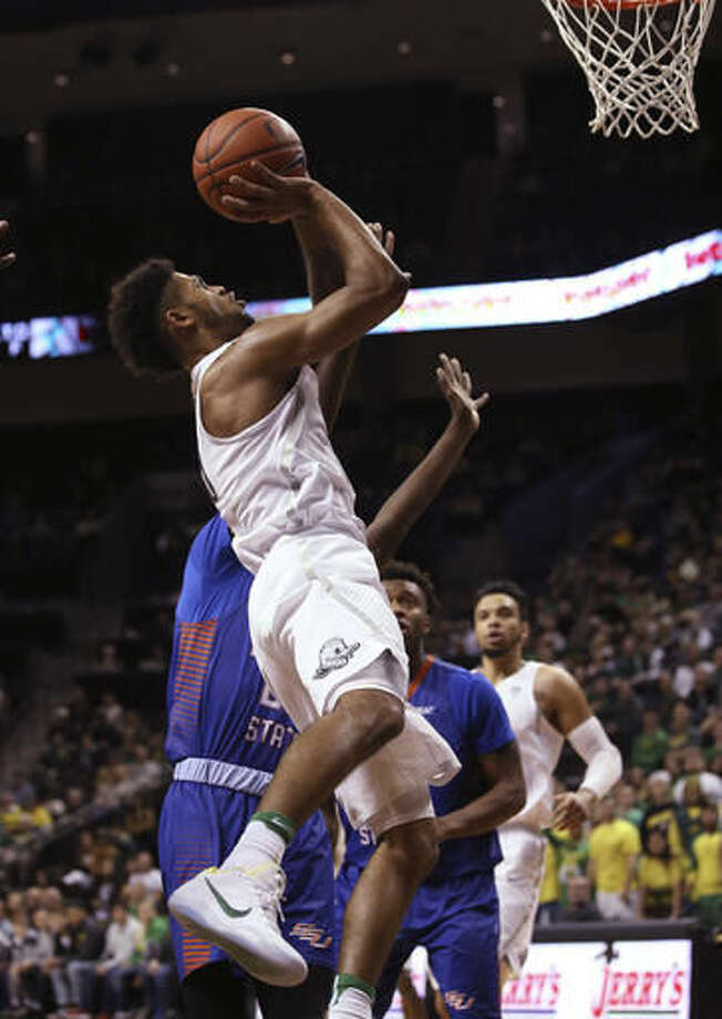 Oregon's Tyler Dorsey goes up for a shot against Savannah State's Marlon Daniel and Kamil Williams during the first half of an NCAA college basketball game Saturday, Dec. 3, 2016, in Eugene, Ore. (AP Photo/Chris Pietsch)