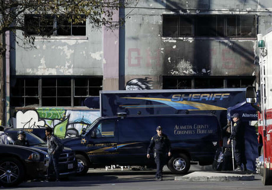 A coroner's van is parked outside of a warehouse after it was destroyed by a fire Saturday, Dec. 3, 2016, in Oakland, Calif. Oakland fire chief Teresa Deloche-Reed said many people were unaccounted for as of Saturday morning and authorities were working to verify who was in the cluttered warehouse when the fire broke out around 11:30 p.m. Friday. (AP Photo/Marcio Jose Sanchez)