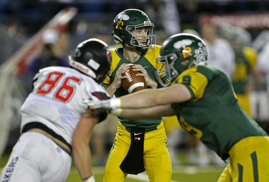 Richland quarterback Paxton Stevens, center, gets set to pass as Richland's Aric Davison, right, blocks Camas' Dylan Ingram (86) during the first half of the Washington Div. 4A high school football championship, Saturday, Dec. 3, 2016, in Tacoma, Wash. (AP Photo/Ted S. Warren)