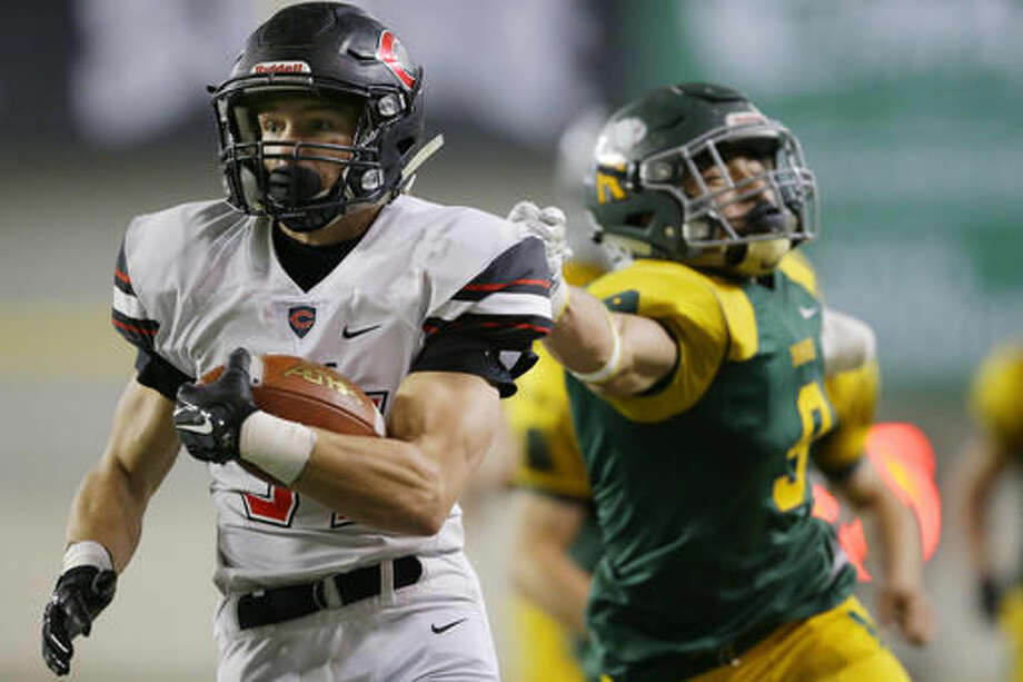 Camas running back Will Schultz, left, escapes the grasp of Richland's Kyle Kirby, right, to run for a touchdown during the second half of the Washington Div. 4A high school football championship, Saturday, Dec. 3, 2016, in Tacoma, Wash. (AP Photo/Ted S. Warren)