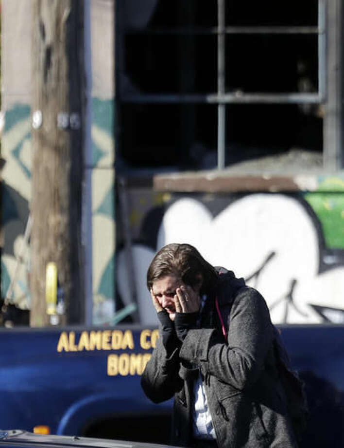 A unidentified man covers his face outside of a warehouse destroyed by a fire Saturday, Dec. 3, 2016, in Oakland, Calif. A deadly fire broke out during a rave at the converted warehouse in the San Francisco Bay Area. (AP Photo/Marcio Jose Sanchez)