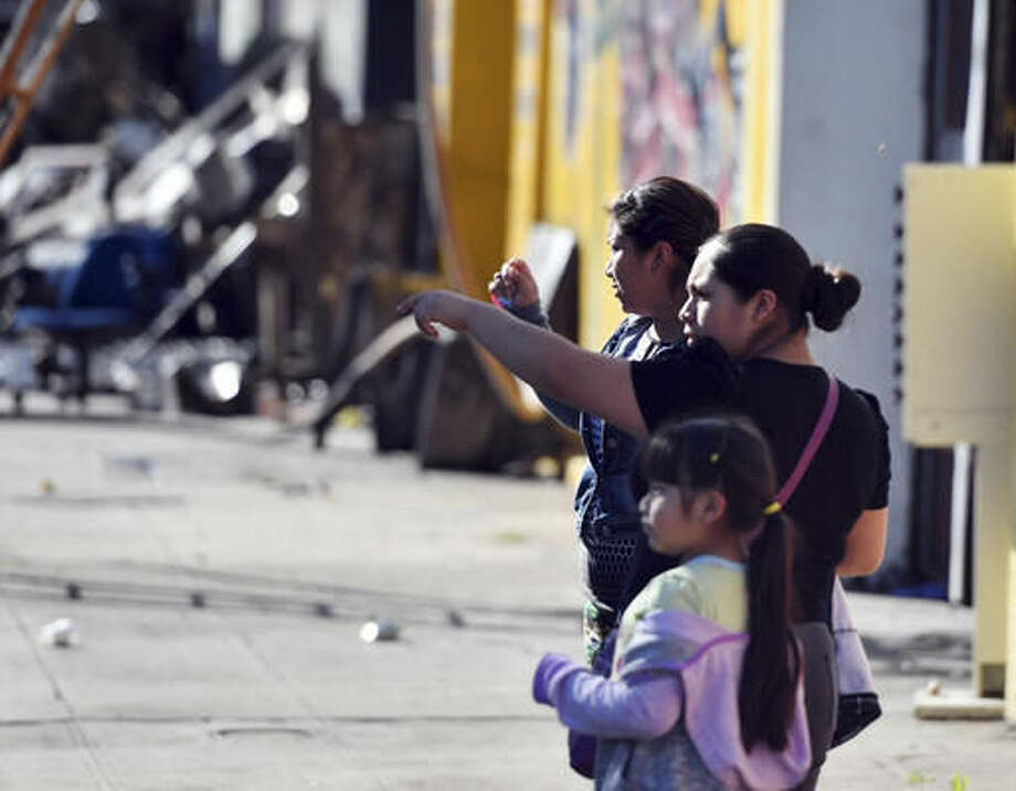 Passersby look at the scene of a warehouse fire Saturday, Dec. 3, 2016, in Oakland, Calif. A deadly fire broke out during a rave at the converted warehouse in the San Francisco Bay Area. (AP Photo/Josh Edelson)