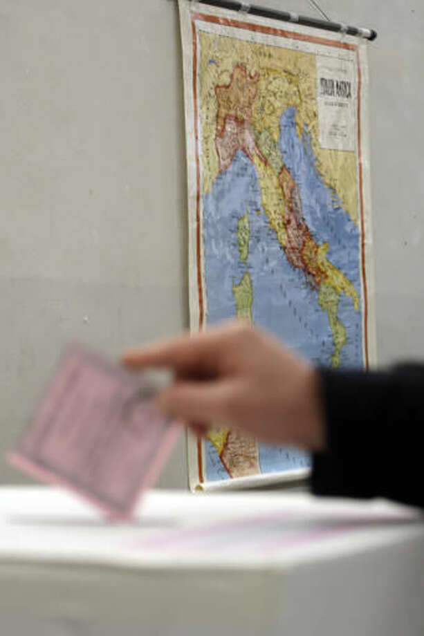 A man casts his ballot as a map of Italy is seen in background at a polling station in Rome, Sunday, Dec. 4, 2016.Italians are voting in a referendum on constitutional reforms that is being closely watched abroad to see if Italy is the next country to reject the political status quo. Premier Matteo Renzi has said he would resign if the reforms are rejected in Sunday's vote, and opposition politicians have vowed to press for a new government if voters reject the proposed constitutional changes. (AP Photo/Gregorio Borgia)