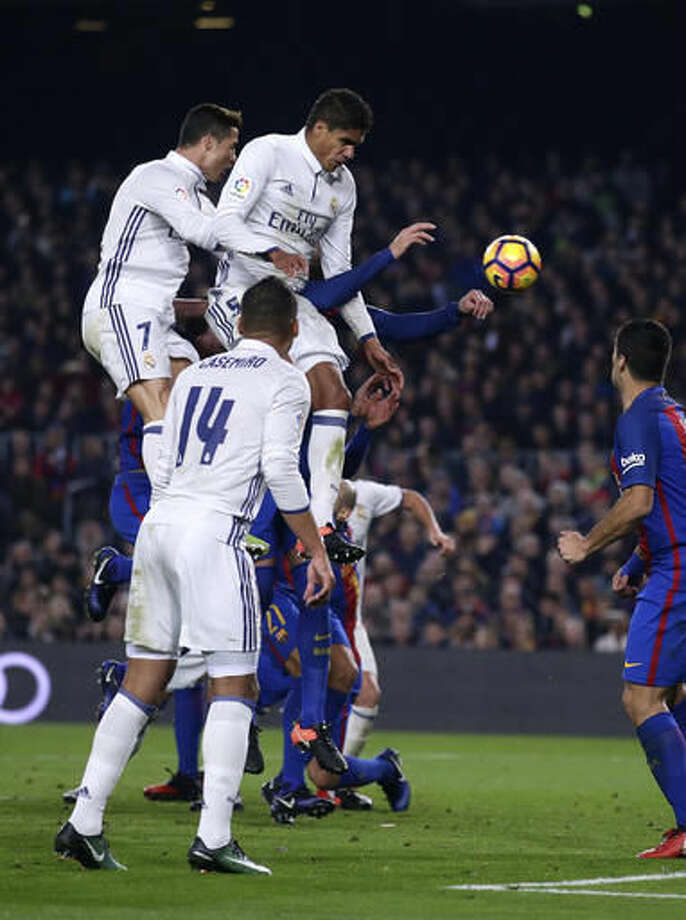 Real Madrid's Raphael Varane,top, and Cristiano Ronaldo, top left, jump to head the ball during the Spanish La Liga soccer match between FC Barcelona and Real Madrid at the Camp Nou in Barcelona, Spain, Saturday, Dec. 3, 2016. (AP Photo/Manu Fernandez)
