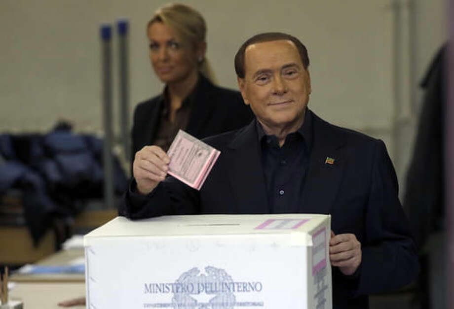 Former Italian Premier Silvio Berlusconi casts his ballot at a polling station in Rome, Sunday, Dec. 4, 2016.Italians are voting in a referendum on constitutional reforms that is being closely watched abroad to see if Italy is the next country to reject the political status quo. Premier Matteo Renzi has said he would resign if the reforms are rejected in Sunday's vote, and opposition politicians have vowed to press for a new government if voters reject the proposed constitutional changes. (AP Photo/Gregorio Borgia)
