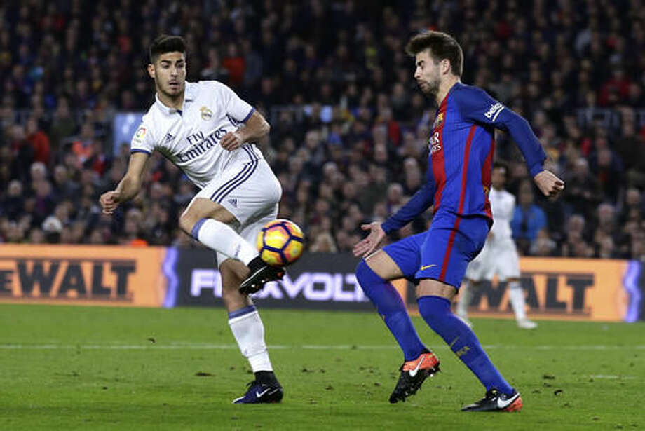 Real Madrid's Marco Asensio, left, goes for the ball with Barcelona's Gerard Pique during the Spanish La Liga soccer match between FC Barcelona and Real Madrid at the Camp Nou in Barcelona, Spain, Saturday, Dec. 3, 2016. (AP Photo/Manu Fernandez)