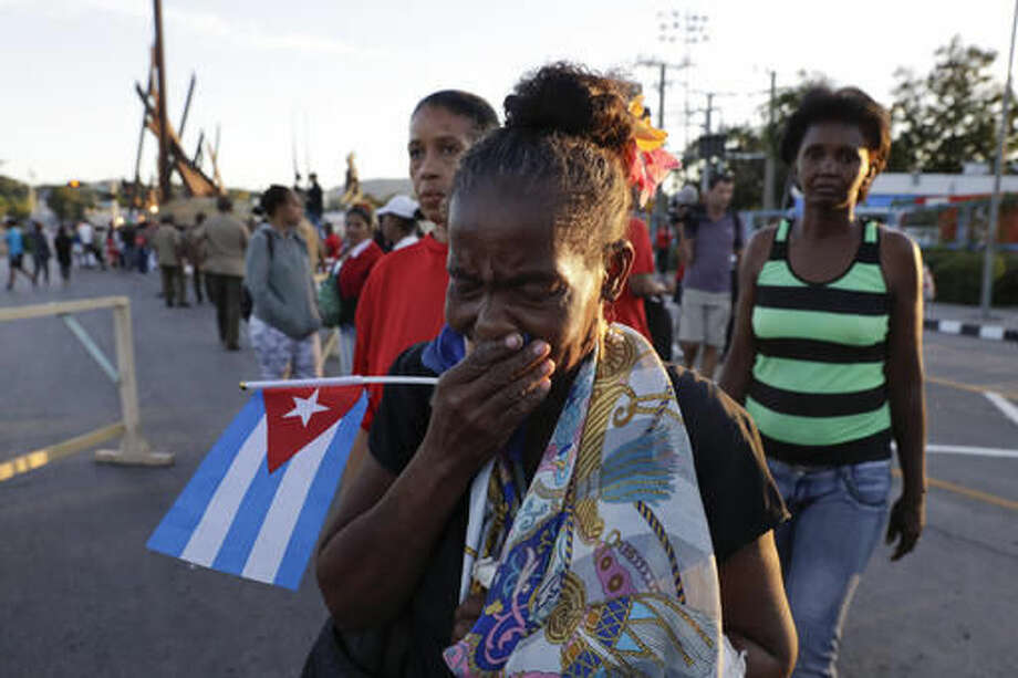 A woman cries after watching the ashes of Fidel Castro leave the Antonio Maceo plaza heading to the Santa Ifigenia cemetery for a private funeral ceremony in Santiago, Cuba, , Sunday, Dec. 4, 2016.(AP Photo/Natacha Pisarenko)