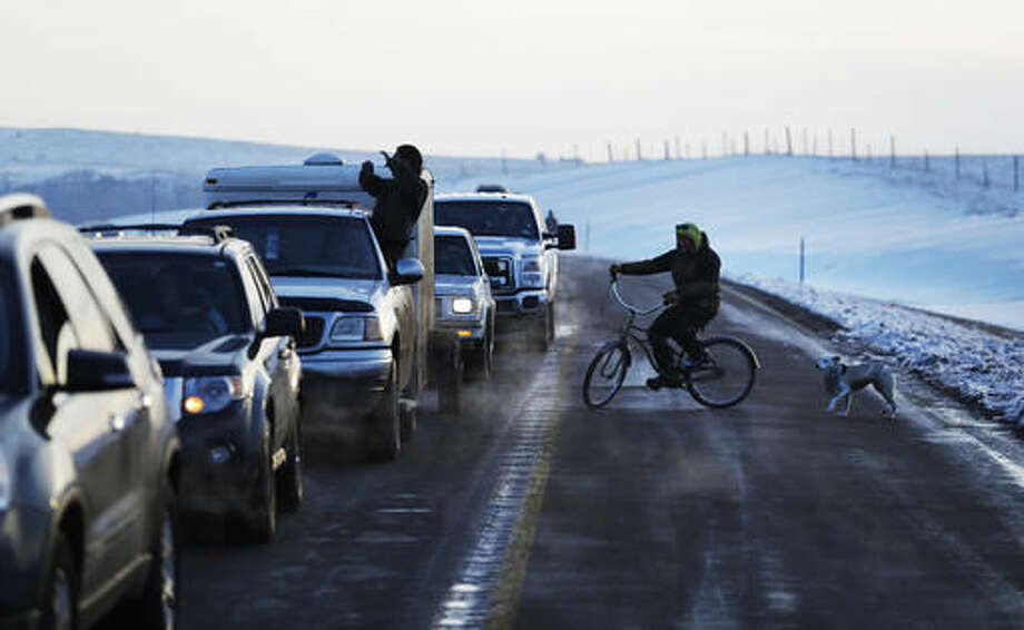 A line of the cars wait to enter the Oceti Sakowin camp where people have gathered to protest the Dakota Access oil pipeline in Cannon Ball, N.D., Saturday, Dec. 3, 2016. (AP Photo/David Goldman)