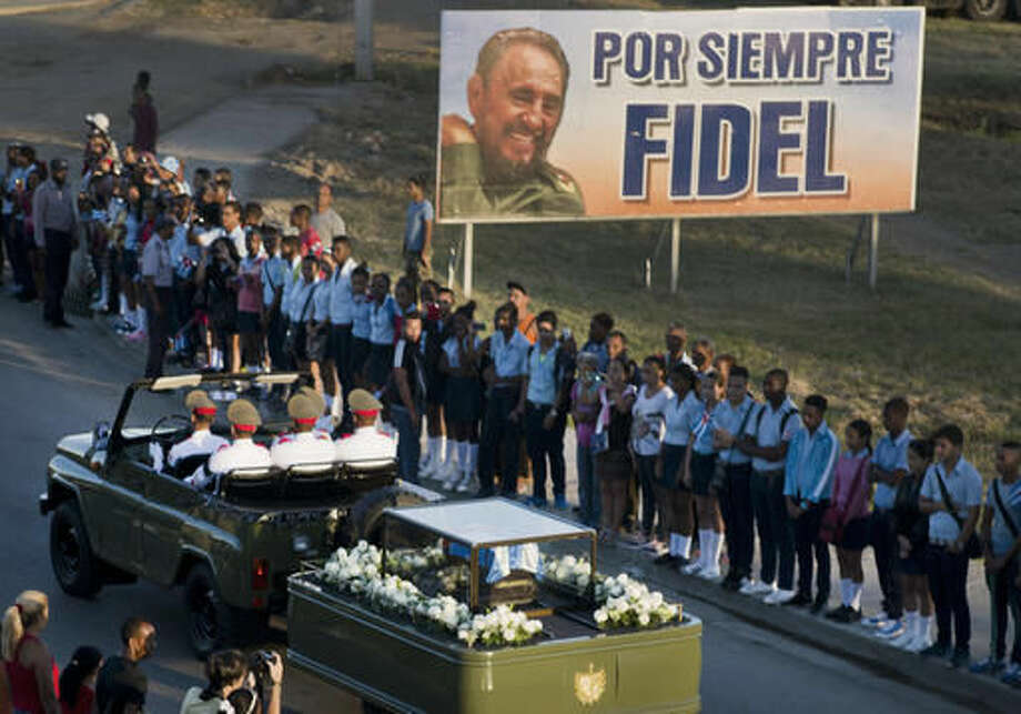 The motorcade carrying the ashes of the late Cuban leader Fidel Castro makes i's final journey towards the Santa Ifigenia cemetery in Santiago, Cuba Sunday, Dec. 4, 2016. Thousands of people lined the short route from the Plaza Antonio Maceo or Plaza of the Revolution to the cemetery where the ashes will be buried in a private ceremony near the grave of Cuba's independence hero Jose Marti. (AP Photo/Ramon Espinosa)