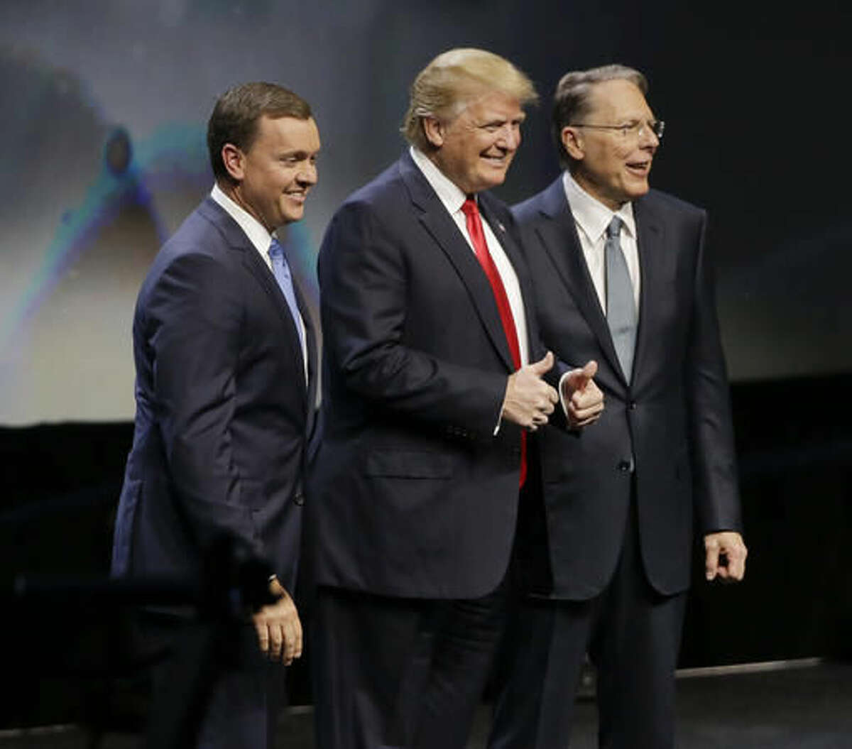FILE - In this May 20, 2016, file photo, then-Republican presidential candidate Donald Trump is introduced by National Rifle Association executive director Chris W. Cox , left, and NRA executive vice president Wayne LaPierre as he takes the stage to speak at the NRA convention in Louisville, Ky. Firearms enthusiasts who embraced Donald Trump's presidential campaign and his full-throated support of the Second Amendment are expecting a sweeping expansion of gun rights under his administration and a Congress firmly controlled by Republicans. (AP Photo/Mark Humphrey, File)