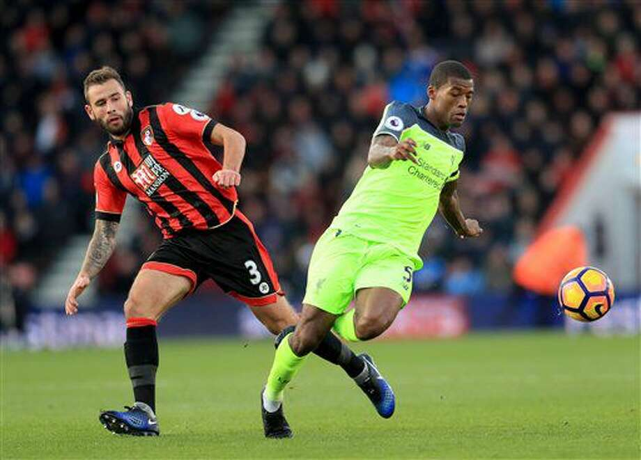Liverpool's Georginio Wijnaldum, right, and AFC Bournemouth's Steve Cook battle for the ball during the English Premier League soccer match at the Vitality Stadium, Bournemouth, England, Sunday Dec. 4, 2016. (Adam Davy/PA via AP)