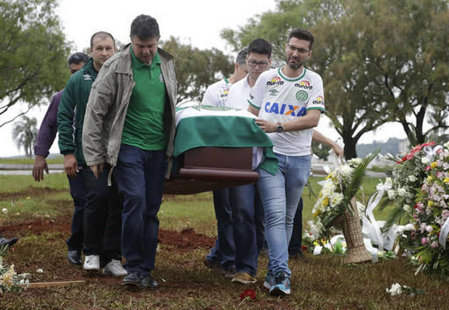 Friends and relatives carry the coffin with the remains of Chapecoense soccer team's late president Sandro Pallaoro, who died in a plane crash in Colombia, at his burial in Chapeco, Brazil, Sunday, Dec. 4, 2016. The accident Monday in the Colombian Andes claimed most of the team's players and staff as it headed to the finals of one of Latin America's most important club tournaments. (AP Photo/Andre Penner)