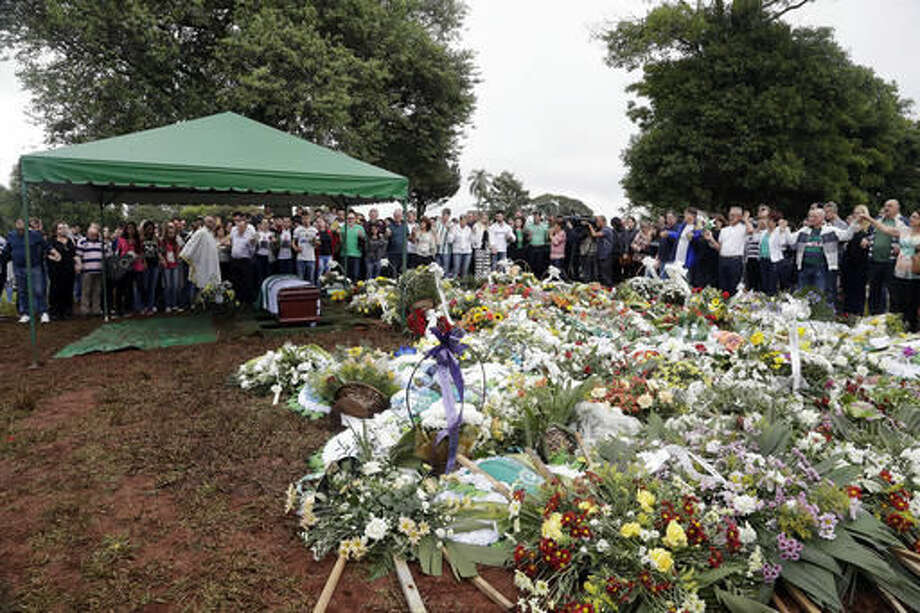 Friends and relatives attend the burial of Chapecoense soccer team's late president Sandro Pallaoro, who died in a plane crash in Colombia, in Chapeco, Brazil, Sunday, Dec. 4, 2016. (AP Photo/Andre Penner)