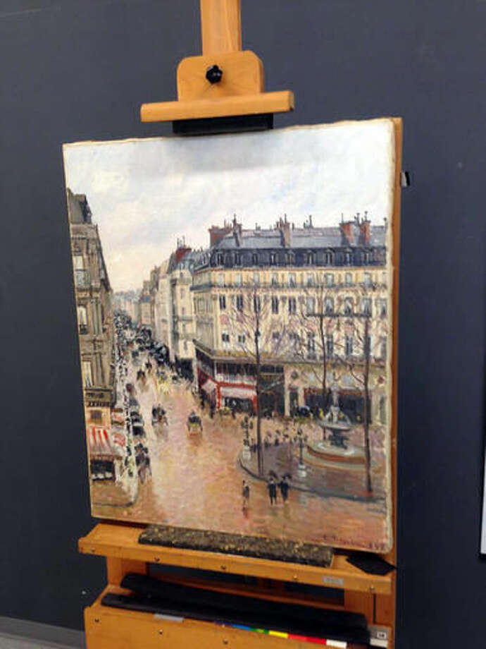 "This Sept. 22, 2014 photo made available by Professor Jonathan Petropolous shows Camille Pissarro's 1897 Impressionist masterpiece, ""Rue Saint-Honoré, dans l'après-midi. Effet de pluie,"" during an examination at the Museo Thyssen-Bornemisza in Madrid. In the 16-year battle over this priceless painting looted by the Nazis, there is one point on which all sides agree: When Lilly Cassirer and her husband fled Germany ahead of the Holocaust in 1939, the Jewish couple had to surrender their masterpiece in exchange for their lives. What they disagree on is who owns the painting now. Are the owners the descendants of Cassirer or the Spanish museum that acquired the painting decades ago in good faith. On Monday, Dec. 5, 2016, the case will be argued in a federal appeals court. (Jonathan Petropolous via AP)"