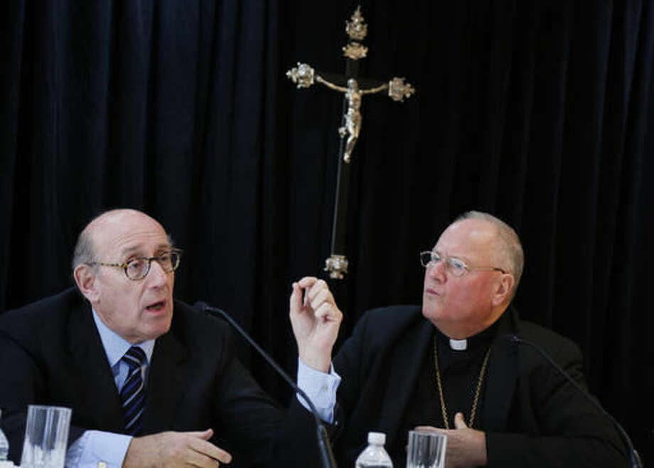 FILE - In this Oct. 6, 2016 file photo, Cardinal Timothy Dolan, Archbishop of New York, right, listens as Kenneth Feinberg speaks to reporters during a news conference in New York announcing a new program intended to provide reconciliation and compensation for victims of sexual abuse by clergy. The new compensation process set up by the Archdiocese of New York itself, potentially the most extensive effort of its kind to date, lets people take claims, often too old for court, to a noted outside mediator while keeping painful details private. (AP Photo/Seth Wenig, File)