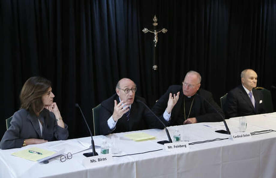 FILE - In this Oct. 6, 2016 file photo, Kenneth Feinberg, second from left, speaks while Camille Biros, left, Cardinal Timothy Dolan, Archbishop of New York, second from right, and former New York City Police Commissioner Raymond Kelly listen during a news conference in New York announcing a new program intended to provide reconciliation and compensation for victims of sexual abuse by clergy. The new compensation process set up by the Archdiocese of New York itself, potentially the most extensive effort of its kind to date, lets people take claims, often too old for court, to a noted outside mediator while keeping painful details private. (AP Photo/Seth Wenig, File)
