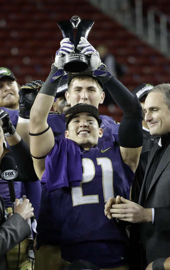 Washington defensive back Taylor Rapp (21) holds the game MVP trophy after Washington's 41-10 win over Colorado in the Pac-12 Conference championship NCAA college football game Friday, Dec. 2, 2016, in Santa Clara, Calif. (AP Photo/Marcio Jose Sanchez)