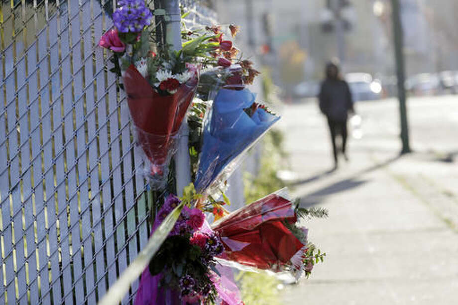 Flowers are placed at the scene of a warehouse fire, Sunday, Dec. 4, 2016, in Oakland, Calif. Officials said they are continuing to search the charred debris from the fatal fire that ripped through a late-night dance party in the converted warehouse earlier in the weekend. (AP Photo/Marcio Jose Sanchez)