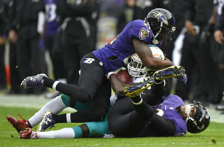 Miami Dolphins running back Jay Ajayi, center, is tackled by Baltimore Ravens free safeties Lardarius Webb, top, and Kendrick Lewis in the first half of an NFL football game, Sunday, Dec. 4, 2016, in Baltimore. (AP Photo/Nick Wass)