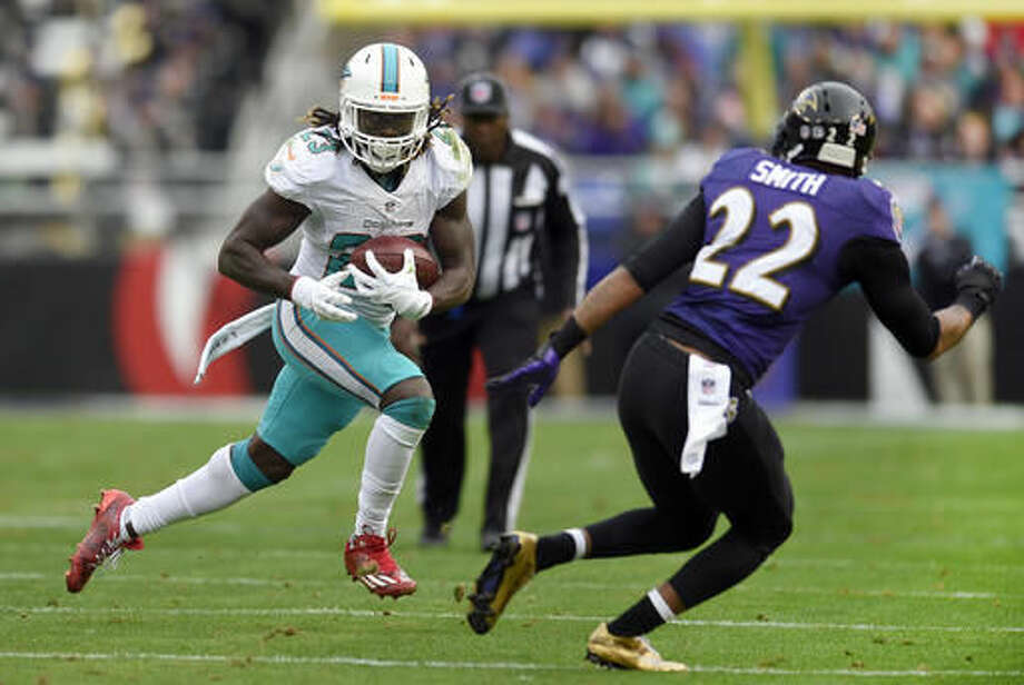 Miami Dolphins running back Jay Ajayi, left, rushes against Baltimore Ravens cornerback Jimmy Smith in the first half of an NFL football game, Sunday, Dec. 4, 2016, in Baltimore. (AP Photo/Nick Wass)