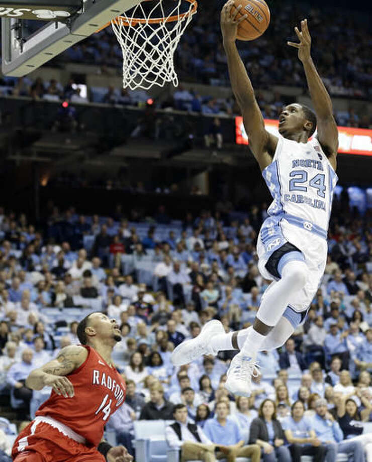 North Carolina's Kenny Williams (24) drives to the basket as Radford's Justin Cousin (14) defends during the first half of an NCAA college basketball game in Chapel Hill, N.C., Sunday, Dec. 4, 2016. (AP Photo/Gerry Broome)