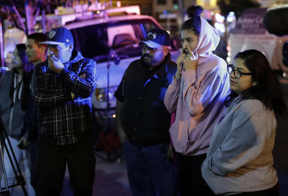 People watch as firefighters and emergency crews work the site of a warehouse fire Saturday, Dec. 3, 2016, in Oakland, Calif. Firefighters struggled to get to bodies in the rubble Saturday, after a deadly fire tore through a converted Oakland warehouse during a late-night electronic music party Friday, making the charred structure unsafe for emergency crews to enter. (AP Photo/Marcio Jose Sanchez)
