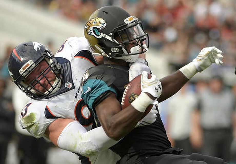 Jacksonville Jaguars running back T.J. Yeldon, right, is stopped by Denver Broncos defensive end Jared Crick during the first half of an NFL football game in Jacksonville, Fla., Sunday, Dec. 4, 2016. (AP Photo/Phelan M. Ebenhack)