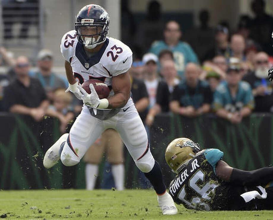 Denver Broncos' Devontae Booker (23) runs for yardage past Jacksonville Jaguars defensive end Dante Fowler (56) during the first half of an NFL football game in Jacksonville, Fla., Sunday, Dec. 4, 2016. (AP Photo/Phelan M. Ebenhack)
