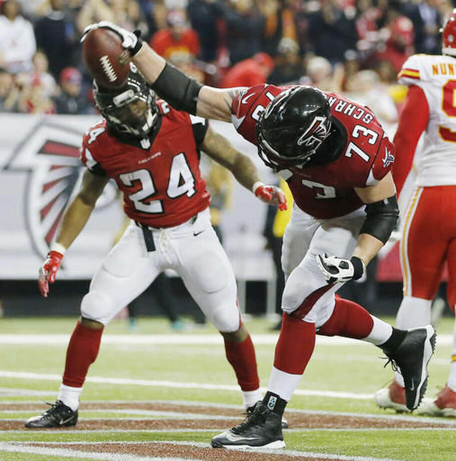 Atlanta Falcons tackle Ryan Schraeder (73) spikes the ball as Atlanta Falcons running back Devonta Freeman (24) looks on after Freeman scored a touchdown against the Kansas City Chiefs during the second half of an NFL football game, Sunday, Dec. 4, 2016, in Atlanta. (AP Photo/John Bazemore)