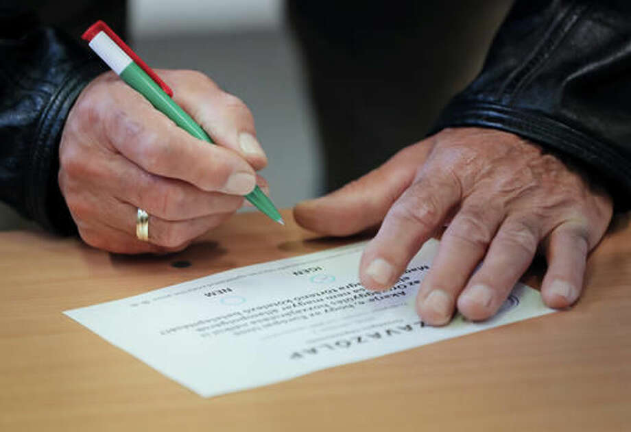 FILE - In this Oct. 2, 2016 file photo a man marks a ballot paper to vote against Hungarian Prime Minister Viktor Orban's policies on migrants in the referendum in Budapest, Hungary, Sunday, Oct. 2, 2016. Orban's Fidesz party failed Tuesday, Nov. 8, 2016 to secure any opposition support on future plans by the European Union to resettle asylum seekers among members of the bloc and fell two votes short of the two-thirds majority necessary in today's vote. (AP Photo/Vadim Ghirda, file)
