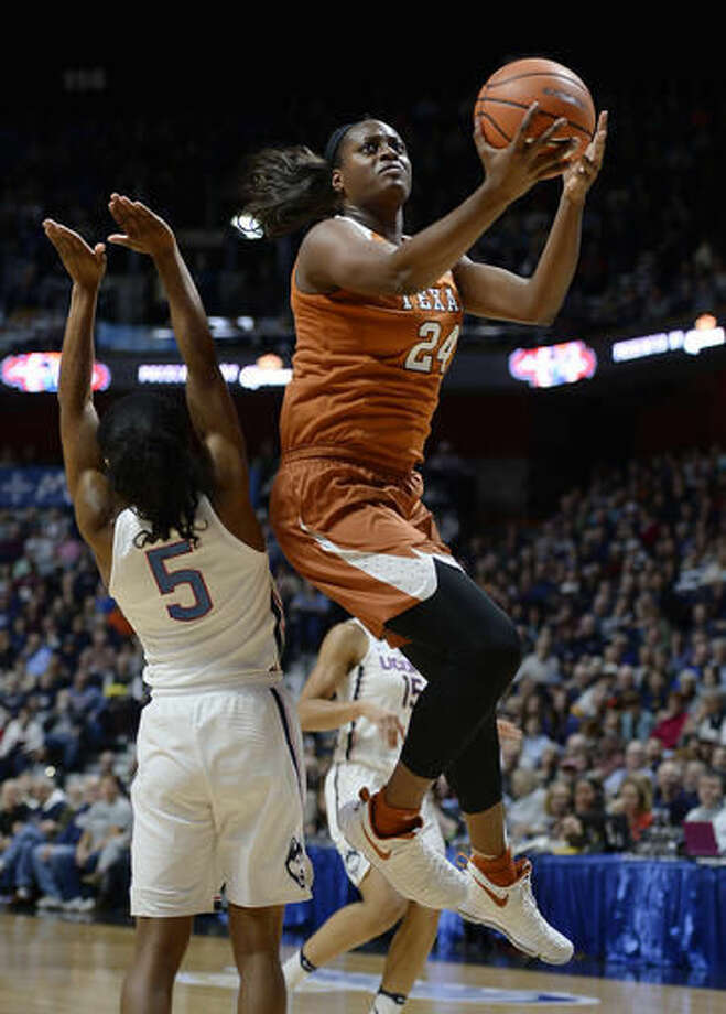 Texas's Joyner Holmes goes up for a basket against Connecticut's Crystal Dangerfield, left, in the first half of an NCAA college basketball game, Sunday, Dec. 4, 2016, in Uncasville, Conn. (AP Photo/Jessica Hill)