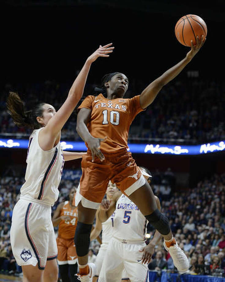 Texas's Lashann Higgs goes up for a basket against Connecticut's Natalie Butler, left, in the first half of an NCAA college basketball game, Sunday, Dec. 4, 2016, in Uncasville, Conn. (AP Photo/Jessica Hill)