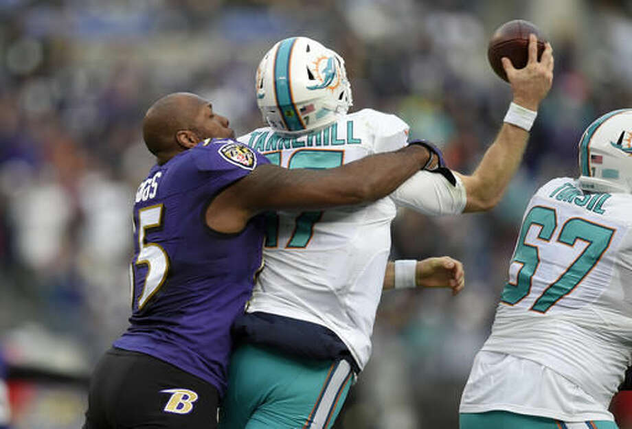 Baltimore Ravens outside linebacker Terrell Suggs, left, tackles Miami Dolphins quarterback Ryan Tannehill after losing his helmet in the second half of an NFL football game, Sunday, Dec. 4, 2016, in Baltimore. (AP Photo/Nick Wass)